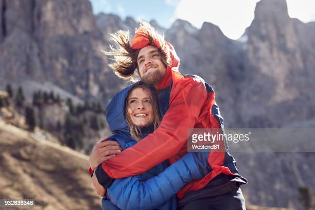happy young couple hugging in windy mountains - jacke stock-fotos und bilder