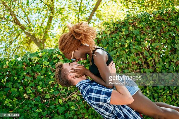 happy young couple hugging outdoors - black men kissing white women stock photos and pictures