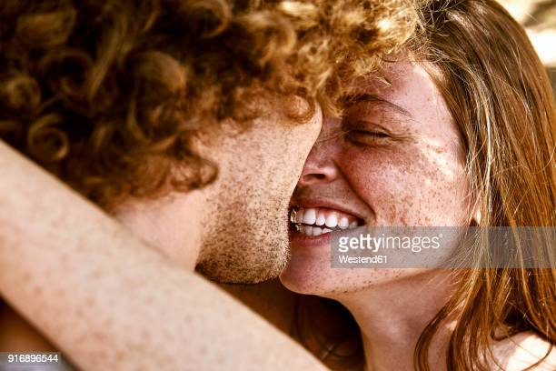 happy young couple hugging - lachen stockfoto's en -beelden