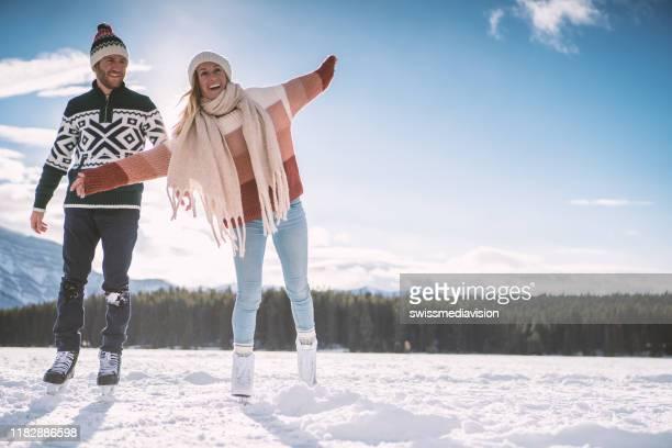 glückliches junges paar eislaufen hand in hand auf gefrorenen see genießen winterspaß - eislauf oder rollschuhlauf stock-fotos und bilder
