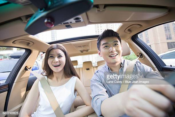 Happy young couple in a car