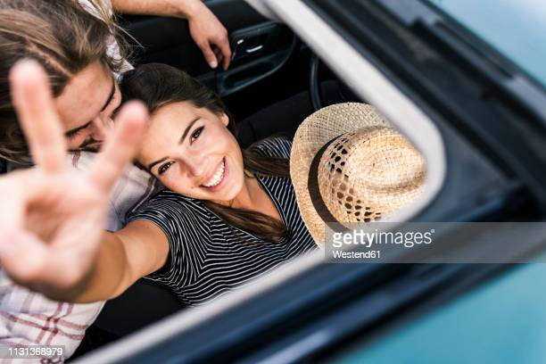 happy young couple in a car seen through sunroof - on the move stock-fotos und bilder