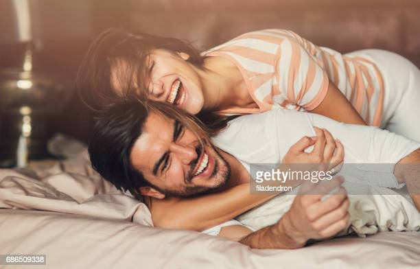 happy young couple in bed - flirtare foto e immagini stock