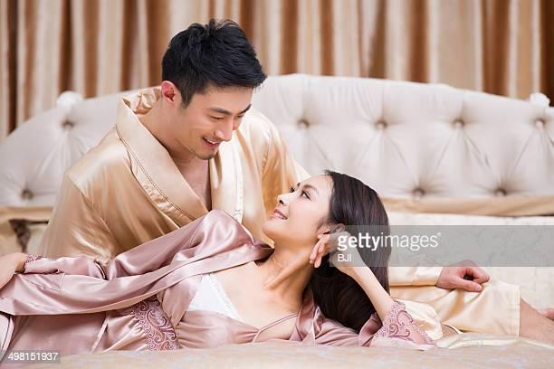happy young couple in bedroom - couple au lit photos et images de collection