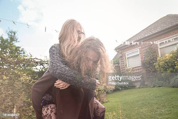 Happy young couple in garden on piggy back