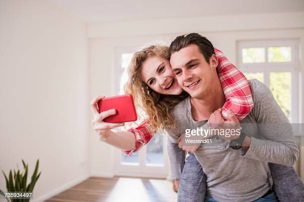 Happy young couple in new home taking a selfie