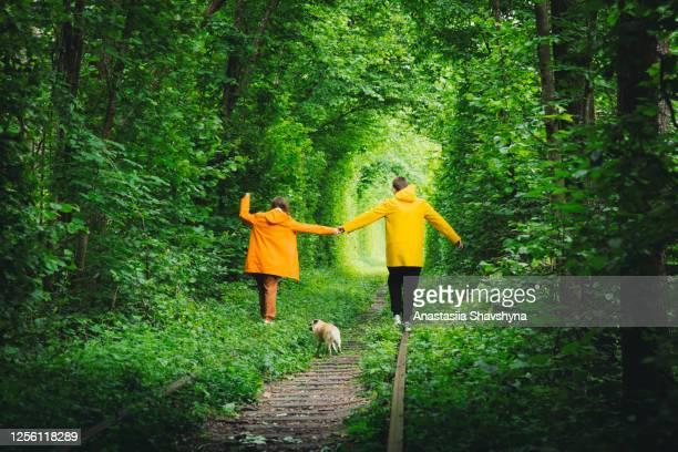 犬とレインコートを着た幸せな若いカップルは、雄大な自然に囲まれた夏の日の出を満たしています - ウクライナ トンネル ストックフォトと画像