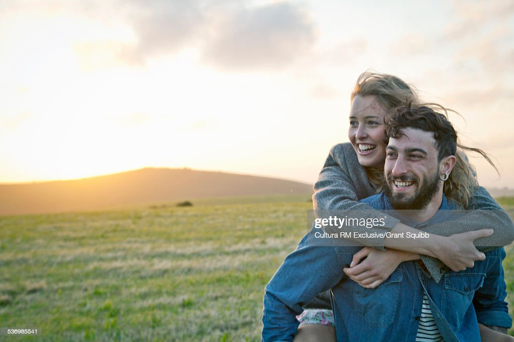 Happy young couple in rural field, Dorset, England : Stock Photo