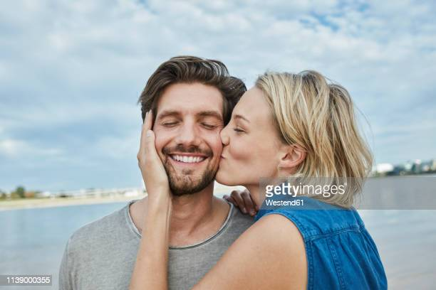 happy young couple kissing on the beach - zärtlich stock-fotos und bilder