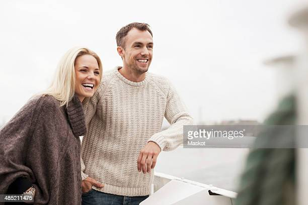 Happy young couple leaning on railing outdoors