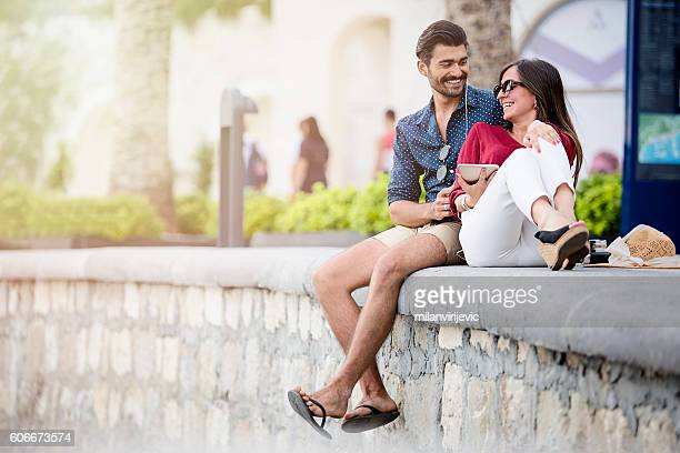 Happy young couple listening music by seaside