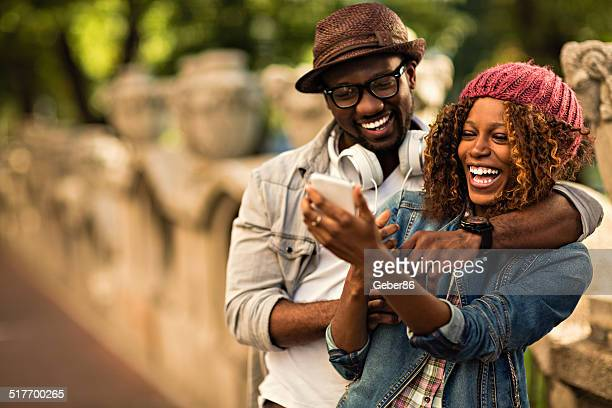 happy young couple looking at mobile phone - a fall from grace stock pictures, royalty-free photos & images