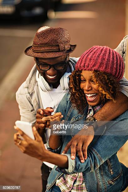 Happy young couple looking at mobile phone