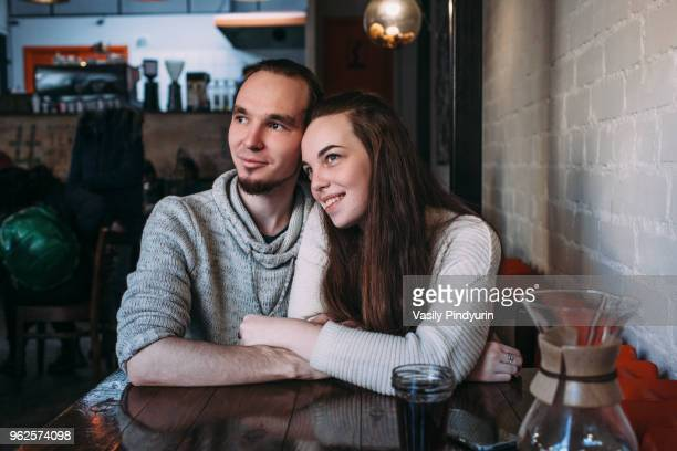 Happy young couple looking away while sitting at cafe