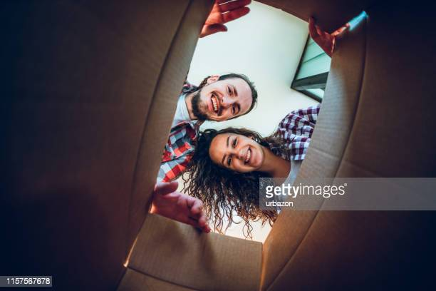 happy young couple looking inside the box - receiving stock pictures, royalty-free photos & images