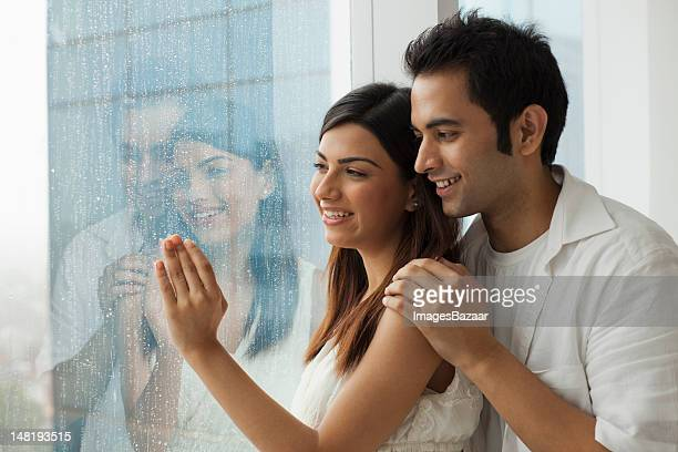 Happy young couple looking through window in rainy day