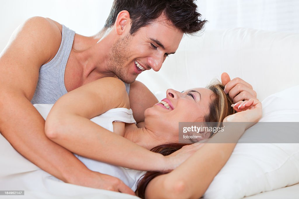 Happy young couple lying down in bed : Stock Photo