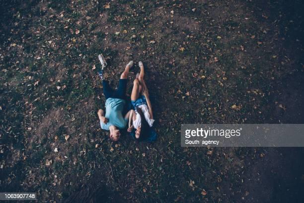 glückliches junges paar auf der wiese liegend - lying down stock-fotos und bilder