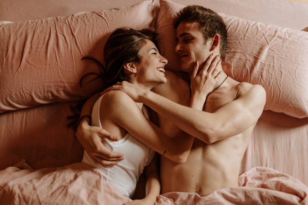 happy young couple lying in bed - man and woman in bed stock pictures, royalty-free photos & images