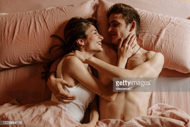 happy young couple lying in bed - erotiek stockfoto's en -beelden