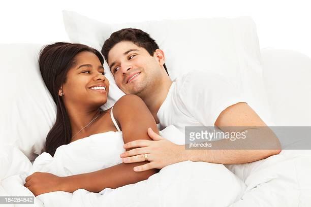 felice giovane coppia sdraiata a letto - abbracciarsi a letto foto e immagini stock