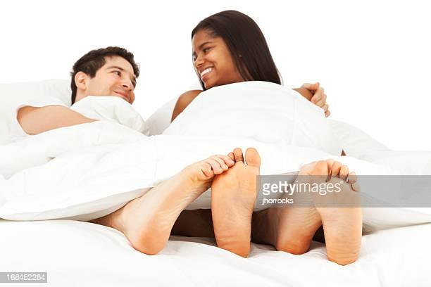 happy young couple lying in bed playing footsie - womens beautiful feet stock photos and pictures