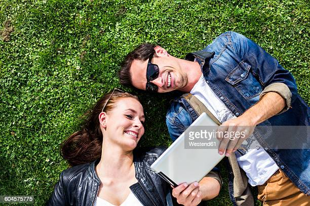 Happy young couple lying in meadow looking at digital tablet
