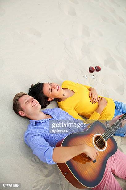 Happy young couple lying on the sand
