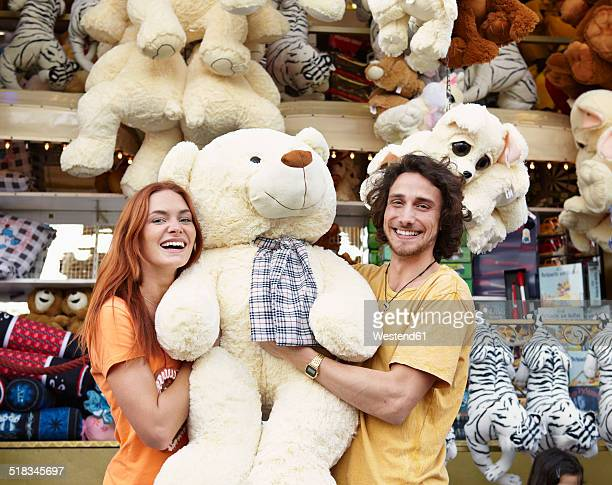 happy young couple on a funfair with large teddy bear - volksfest stock-fotos und bilder