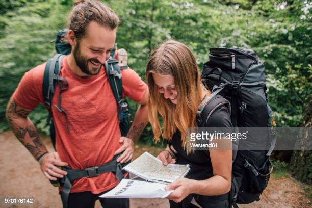 happy young couple on a hiking trip reading map - karte navigationsinstrument stock-fotos und bilder