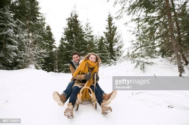 happy young couple on sledge in winter forest - schlitten stock-fotos und bilder