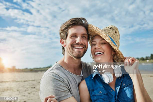 happy young couple on the beach - mid adult men stock-fotos und bilder