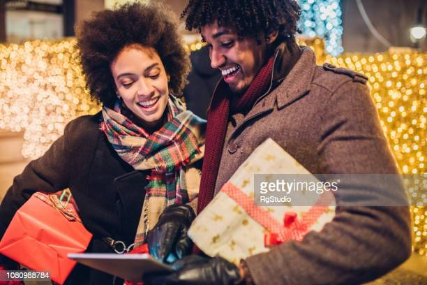 Happy young couple online shopping for Christmas presents with a tablet