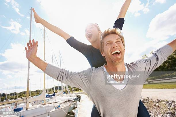 Happy young couple outdoors with arms outstretched