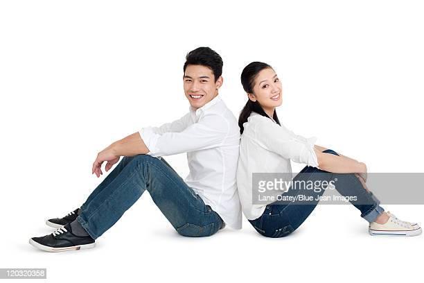 happy young couple - 背中合わせ ストックフォトと画像