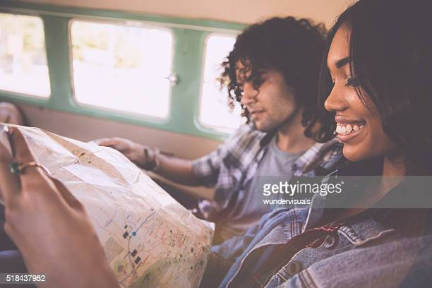 Happy young couple planning road trip in a vintage van