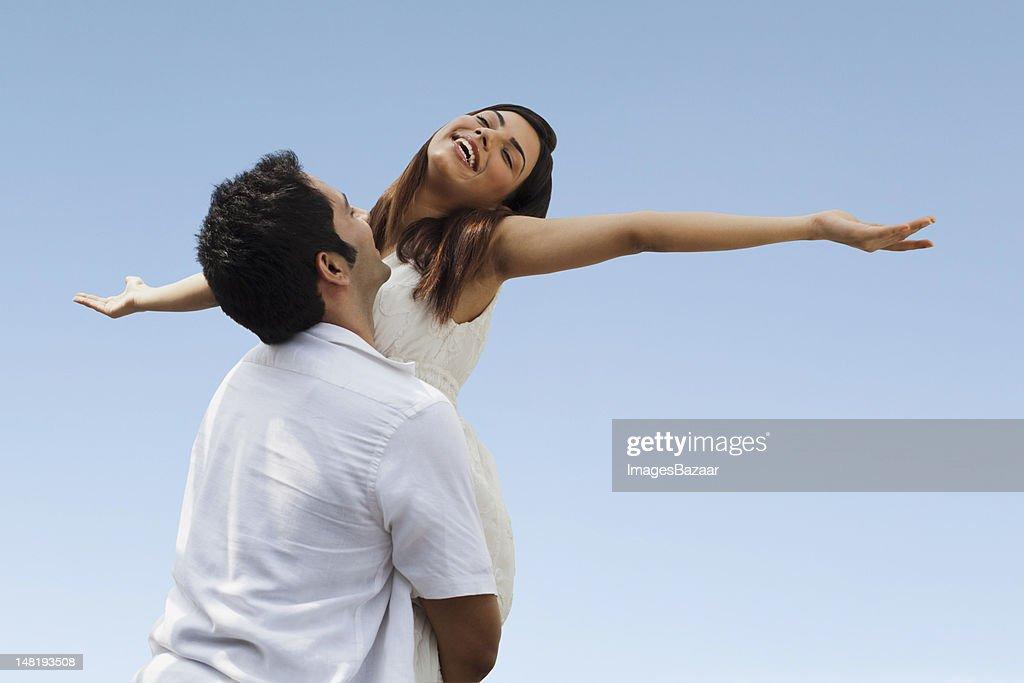 幸せな若いカップルトランプアゲインストブルースカイ : ストックフォト