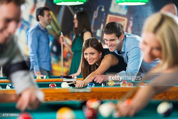 Happy young couple playing billiard together.