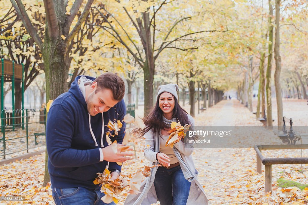 happy young couple playing in autumn park : Stock Photo