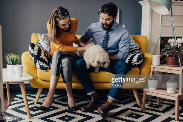 Happy young couple playing with their dog