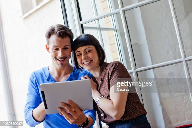gelukkige jonge paar portret kijken naar digitale tablet - goed nieuws stockfoto's en -beelden