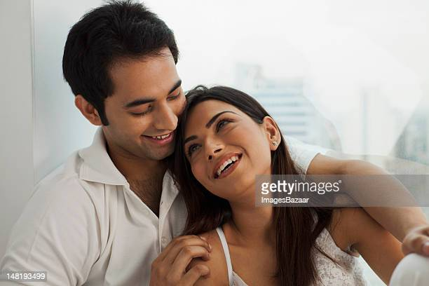 Happy young couple relaxing by window