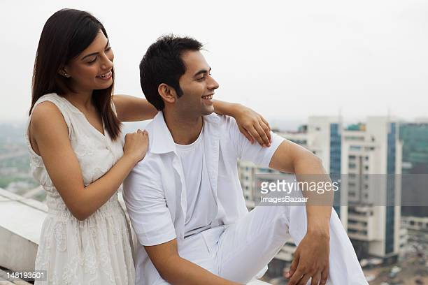 Happy young couple relaxing on balcony