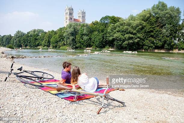Happy young couple relaxing on the riverbank