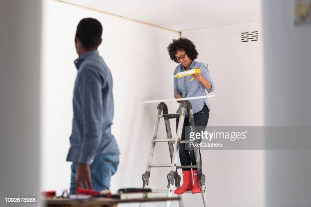 happy young couple renovating living room together attaching new cornice - architectural cornice stock photos and pictures