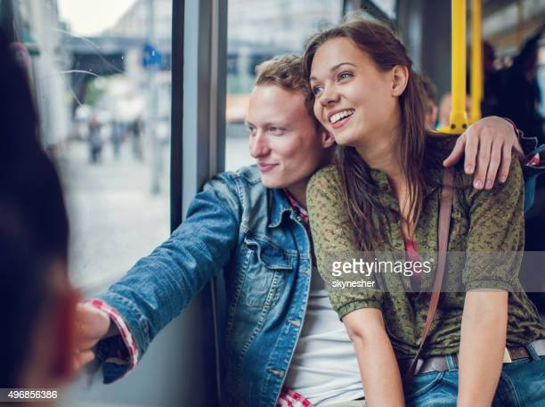 Happy young couple riding in bus and looking through window.