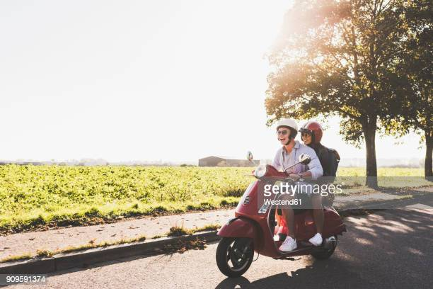happy young couple riding motor scooter on country road - motor scooter stock pictures, royalty-free photos & images