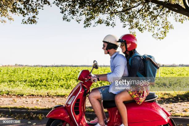 Happy young couple riding motor scooter with backpack on the back