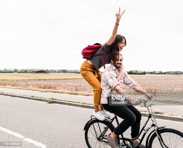 happy young couple riding together on one bicycle on country road - fahrrad stock-fotos und bilder