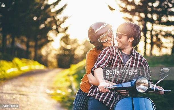 Happy young couple riding vintage motorcycle